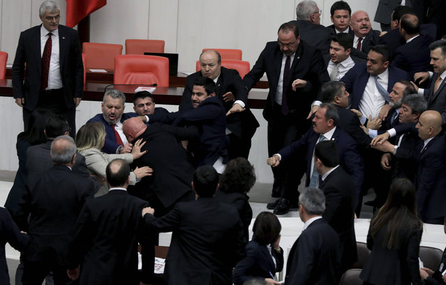 Legislators push each other as a brawl breaks out in Turkey's parliament in Ankara, Turkey, Wednesday, March 4, 2020. A fight broke out in the Turkish parliament between lawmakers from opposing parties during a tense discussion about Turkey's military involvement in northwest Syria. (Photo by AP Photo/Stringer)