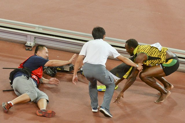 Usain Bolt of Jamaica (R) gets up after being knocked over by a cameraman (L) on a Segway as he celebrates after winning the men's 200 metres final during the 15th IAAF World Championships at the National Stadium in Beijing, China, August 27, 2015. (Photo by Reuters/Stringer)