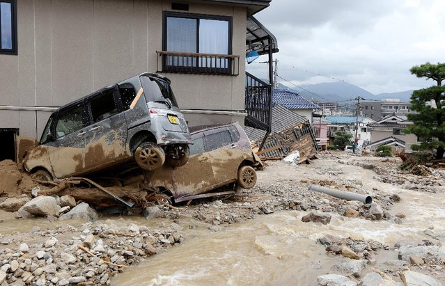 Cars damaged by a landslide lie in mud and debris after heavy rains hit the city of Hiroshima, western Japan, on August 20, 2014. (Photo by AFP Photo/Jiji Press)