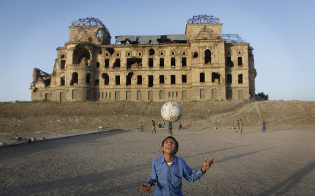 Afghan children play soccer in front of the  war-damaged Darul Aman Palace in the suburbs of Kabul, Afghanistan, Wednesday, June 8, 2011. (Photo by Gemunu Amarasinghe/AP Photo)