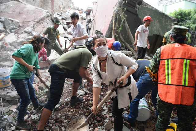 Rescuers, firefighters, policemen, soldiers and volunteers remove rubble and debris from a flattened building in search of survivors after a powerful quake in Mexico City on September 19, 2017. A devastating quake in Mexico on Tuesday killed more than 100 people, according to official tallies, with a preliminary 30 deaths recorded in the capital where rescue efforts were still going on. (Photo by Ronaldo Schemidt/AFP Photo)
