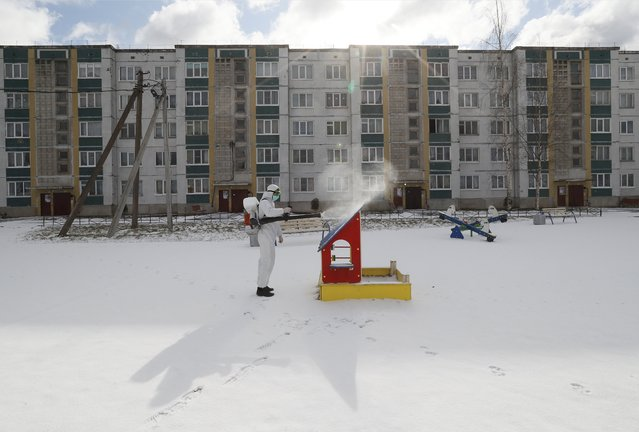 Specialists of the Veterinary Service of the Leningrad region wearing protective hazmat suits spray disinfectant at a playground in Izvora, outside St. Petersburg, Russia, 04 April 2020. The Russian government has approved legal amendments to increase liability for quarantine violators amid the ongoing pandemic of the COVID-19 disease caused by the SARS-CoV-2 coronavirus. (Photo by Anatoly Maltsev/EPA/EFE)