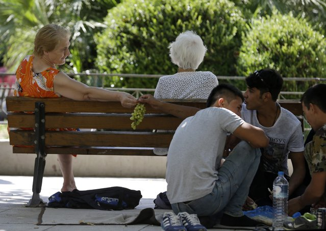 A local resident offers grapes to an Afghan migrant as they sit at Victoria square, Athens, Wednesday, September 2, 2015, where many migrants stay temporarily before continuing their trip to more prosperous European countries. The country has borne the brunt of a massive refugee and migration flow of people heading into the European Union, with more than 200,000 people arriving so far this year. (Photo by Thanassis Stavrakis/AP Photo)