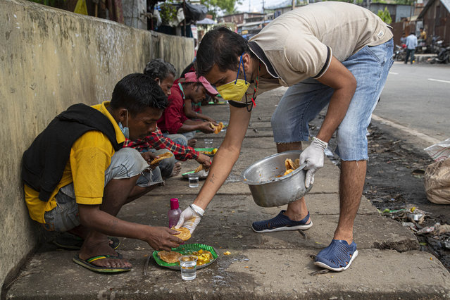 A man distributes food to homeless people on a pavement during a nationwide lockdown to curb the spread of new coronavirus in Gauhati, India, Sunday, April 19, 2020. (Photo by Anupam Nath/AP Photo)