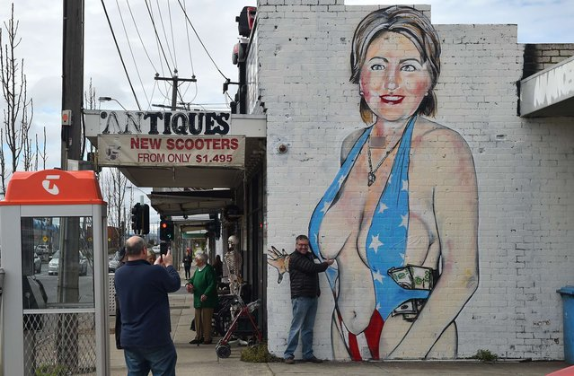 A man poses for a photograph in front of a mural of Democrat US presidential nominee Hillary Clinton clad in a swimsuit bearing the colours of the US flag in West Footscray in Melbourne on July 30, 2016. An Australian mural of US presidential nominee Hillary Clinton in a revealing, stars and stripes swimsuit may be taken down, after it has reportedly been deemed offensive. (Photo by Paul Crock/AFP Photo)