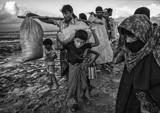 A Rohingya refugee boy carries his belongings as he arrives with his family after crossing the Naf River at Shah Porir Dwip on September 21, 2017 in Cox's Bazar, Bangladesh. (Photo by Kevin Frayer/Getty Images)