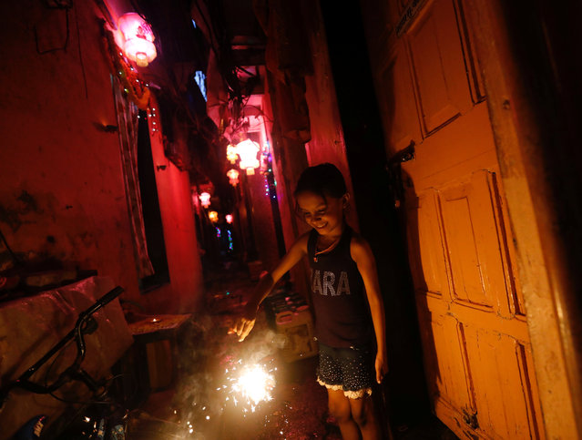 A girl plays with firecracker on the eve of the Hindu festival of Diwali in a slum in Mumbai, October 18, 2017. (Photo by Danish Siddiqui/Reuters)