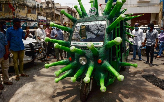 A municipal worker drives a coronavirus-themed auto-rickshaw in a street of a residential area after the government eased a nationwide lockdown imposed as a preventive measure against the COVID-19 coronavirus, in Chennai on May 20, 2020. (Photo by Arun Sankar/AFP Photo)