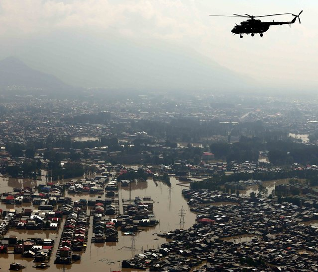 In this handout photograph released by the Ministry of Defence on September 13, 2014, An Indian Air Force Mi-17 flies over floodwaters during a rescue and relief mission over Srinagar. Rescuers struggled to reach more than 200,000 people still stranded in Indian Kashmir as deadly floodwaters receded, revealing horrific devastation in the Himalayan region including neighbouring Pakistan, officials said. (Photo by Vijay Kumar/AFP Photo/Ministry of Defence)