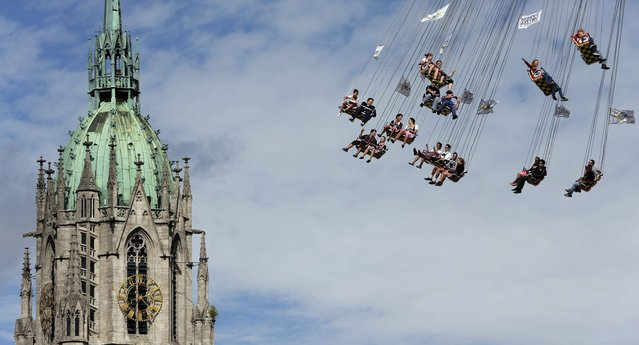People ride a merry-go-round in front of St. Paul church at the 181st Oktoberfest beer festival in Munich, southern Germany, Saturday, September 20, 2014. (Photo by Matthias Schrader/AP Photo)