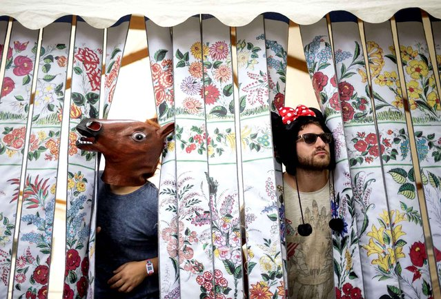 Festival-goers peep from a folding screen in Hungaricum Village on Shipyard Island, the venue of the 24th Sziget (Island) Festival in Northern Budapest, Hungary, Thursday, August 11, 2016. The venue is one of the biggest cultural events of Europe offering art exhibitions, theatrical and circus performances and above all concerts in eight days. (Photo by Balazs Mohai/MTI via AP Photo)
