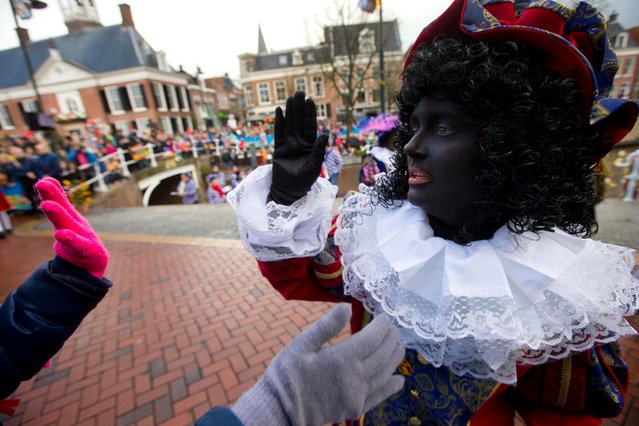 A Black Pete interacts with children during the arrival of Sinterklaas, or Saint Nicholas, in in Dokkum, northern Netherlands, Saturday, November 18, 2017. Sinterklaas and his helper Black Pete are at the center of a long- time controversy because Pete is often played by white people in blackface makeup. (Photo by Peter Dejong/AP Photo)