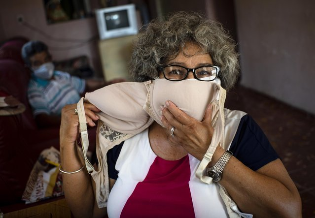 Idania Espanola, 63, poses for a photo showing a bra that she will adapt into two face masks, amid the spread of the new coronavirus in Cojimar, Cuba, east of Havana, Tuesday, March 31, 2020. (Photo by Ramon Espinosa/AP Photo)