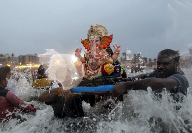 Devotees carry an idol of the Hindu god Ganesh, the deity of prosperity, into the Arabian Sea on the fifth day of the ten-day-long Ganesh Chaturthi festival in Mumbai, India, September 21, 2015. (Photo by Danish Siddiqui/Reuters)