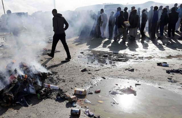 "Smoke rises from burning rubbish as migrants queue during the distribution of food at the makeshift camp called ""The New Jungle"" in Calais, France, September 19, 2015. (Photo by Regis Duvignau/Reuters)"