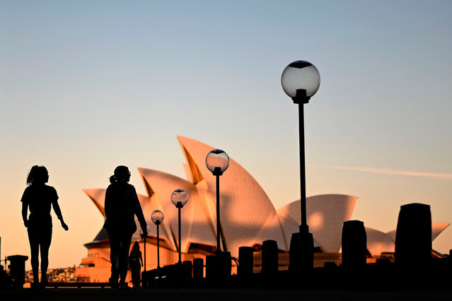 Sunset hues fall on the landmark Sydney Opera House as visitors walk past as on Circular Quay, usually packed with tourists, in Sydney on June 16, 2020. (Photo by Saeed Khan/AFP Photo)