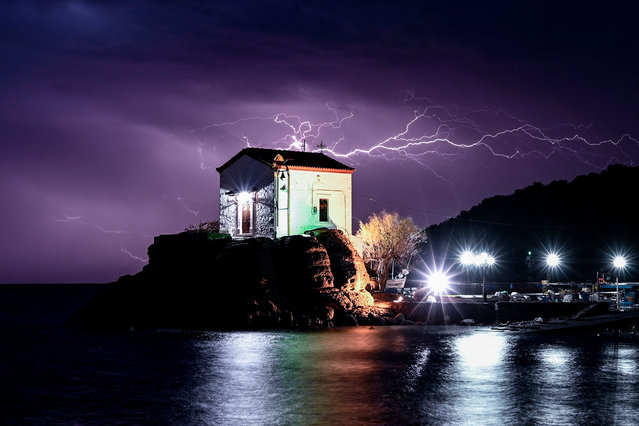 Lightning strikes behind the chapel of Panagia Gorgona in the village of Skala Sykamias, north of Lesbos, on February 27, 2020. (Photo by Aris Messinis/AFP Photo)