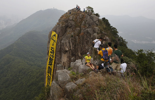 """Hikers take pictures of the yellow banner with the words reading: """"I want genuine universal suffrage"""" in Chinese and """"Umbrella Movement"""" in English hanging on the face of Lion Rock mountain in Hong Kong Thursday, October 23, 2014. Democracy activists hung the banner on the mountain in support of the protest movement in which thousands of demonstrators have camped out on the streets of the southern Chinese financial center for nearly a month to press their demands for greater democracy. (Photo by Kin Cheung/AP Photo)"""