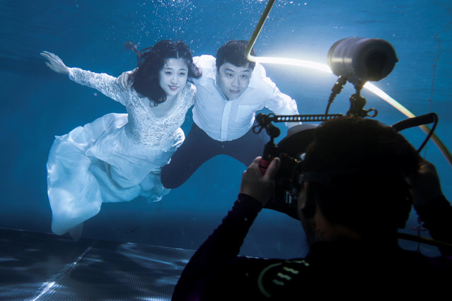 Cao Ri and Xu Jiaqian have a wedding photograph taken in a pool at the Qianyishi Underwater Photography Studio in Beijing, China on September 7, 2017. (Photo by Thomas Peter/Reuters)