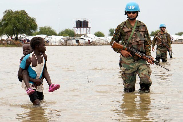 A girl holding a child walks past UN peacekeepers, after heavy rains in the town of Pibor, Boma state, South Sudan, November 6, 2019. (Photo by Andreea Campeanu/Reuters)