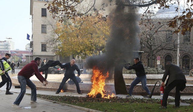Bystanders attempt to put out flames engulfing an unidentified woman after she set herself on fire in front of the Bulgarian presidency building in Sofia November 3, 2014. The woman is now in critical condition in the hospital, local media reported. The reasons for her self-immolation is yet unknown. (Photo by Romeo Cholakov/Reuters)