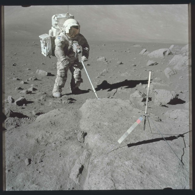 Scientist-astronaut Harrison Schmitt, Apollo 17 lunar module pilot, uses an adjustable sampling scoop to retrieve lunar samples during the second Apollo 17 extravehicular activity in this December 12, 1972 NASA handout photo. (Photo by Reuters/NASA)