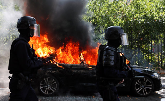 French CRS riot police officers walk past a burning car during a demonstration of the yellow vests movement in Paris, France on September 12, 2020. (Photo by Gonzalo Fuentes/Reuters)