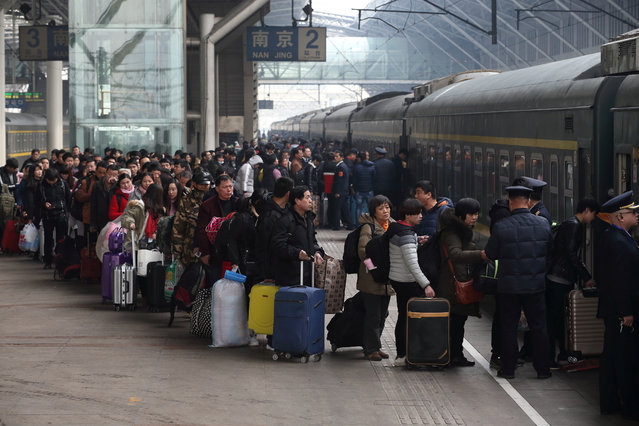 People wait in line to board a train at Nanjing railway station as the travel rush for Chinese Lunar New Year, or Spring festival, begins, in Jiangsu province, China on February 1, 2018. (Photo by Reuters/China Daily)