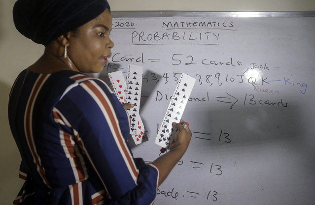 Mathematics teacher Basirat Olamide Ajayi, 36, teaches probability theory with the aid of playing cards, online via her mobile phone from her house in Lagos, Nigeria Saturday, August 15, 2020. The teacher from a Lagos public school is helping students across the country, and internationally, learn math virtually during coronavirus restrictions that have prevented most children from returning to class in Nigeria. (Photo by Sunday Alamba/AP Photo)