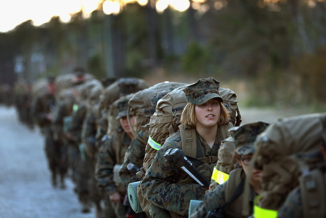 Pfc. Schevlle Woodard from Grand Prairie, Texas prepares to head out on a 15-kilometer night march with male and female Marines during Marine Combat Training (MCT) on February 21, 2013 at Camp Lejeune, North Carolina.  Since 1988 all non-infantry enlisted male Marines have been required to complete 29 days of basic combat skills training at MCT after graduating from boot camp. MCT has been required for all enlisted female Marines since 1997. About six percent of enlisted Marines are female.  (Photo by Scott Olson)