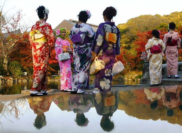 Tourists, dressed in traditional Japanese kimonos, stand in a park in Kyoto, western Japan November 19, 2014. (Photo by Thomas Peter/Reuters)