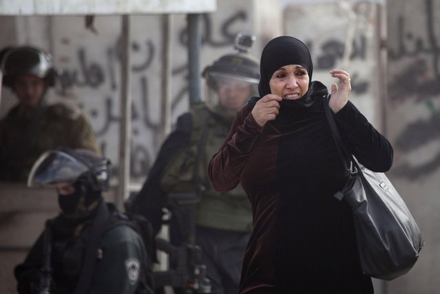 A Palestinian woman flinches as Israeli border policemen clash with protesters opposed to Israeli restrictions on the Al-Aqsa Mosque in Jerusalem, at the Qalandia checkpoint near the West Bank city of Ramallah, Friday, November 21, 2014. (Photo by Majdi Mohammed/AP Photo)