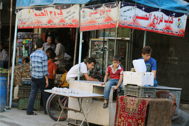 """A boy looks on, inside a market in the rebel-held al-Shaar neighbourhood of Aleppo, Syria, September 17, 2016. The sign reads in Arabic: """"Hussein's Kebab and chicken"""". (Photo by Abdalrhman Ismail/Reuters)"""