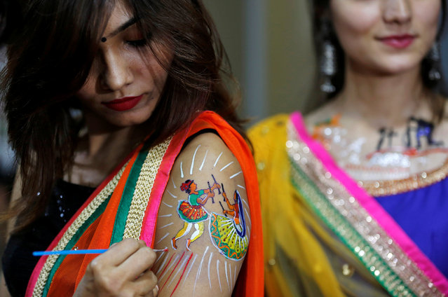 A girl gets her arm sketched with a body paint tattoo depicting the traditional Dandiya dance, ahead of Navratri, a festival when devotees worship the Hindu goddess Durga, in Ahmedabad, India, September 25, 2016. (Photo by Amit Dave/Reuters)