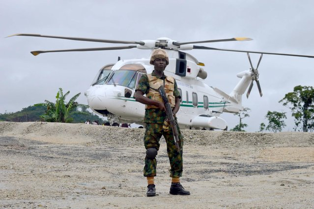A soldier guards the presidential helicopter during the commissioning of the construction of a new superhighway in Cross river state, Nigeria, October 20, 2015. (Photo by Reuters/Stringer)