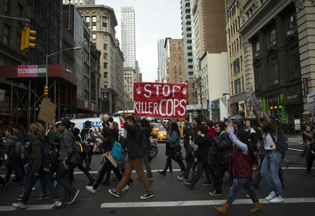 People march with signs during a protest march through the streets of Manhattan against the verdict announced in the shooting death of Michael Brown, in New York, December 1, 2014. (Photo by Mike Segar/Reuters)