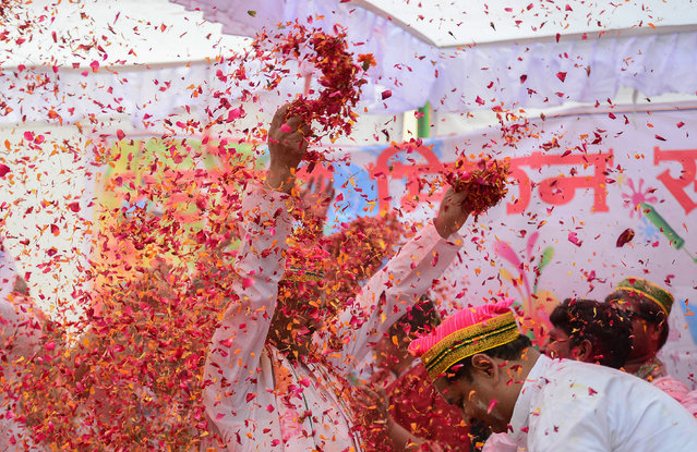 Flower petals and coloured powder is thrown around at an event to celebrate the Hindu festival of Holi for children with cerebral palsy organized by the Trishla Foundation in Allahabad on February 25, 2018. (Photo by Sanjay Kanojia/AFP Photo)
