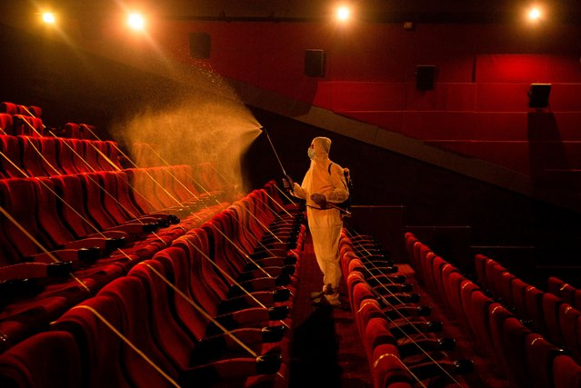 A worker disinfects a movie theatre before its reopening to the public in the southern Iraqi city of Basra on October 14, 2020, following an easing of restrictions imposed by the authorities in a bid to stem the spread of the novel coronavirus. (Photo by Hussein Faleh/AFP Photo)