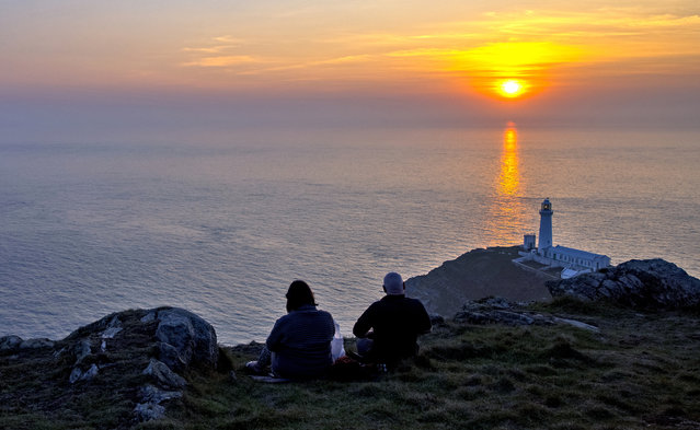 People watch the sun set behind South Stack lighthouse on the Isle of Anglesey, North Wales on September 21, 2020. (Photo by Peter Byrne/PA Images via Getty Images)