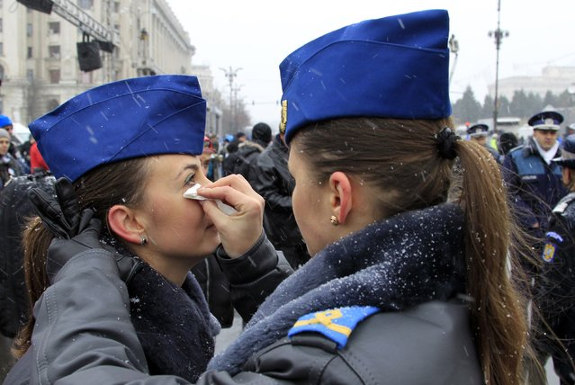 A member of the air force helps her colleague with her make-up before a military parade celebrating Romania's National Day in Bucharest December 1, 2014. (Photo by Radu Sigheti/Reuters)