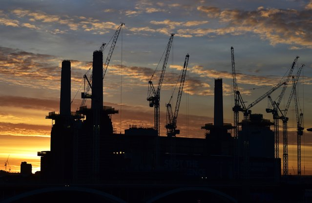 Battersea Power Station is seen at dawn, surrounded by cranes and with one of it's four iconic chimneys missing, in London, December 9, 2014. The decommissioned coal-fired power station, not used since 1983, is being redeveloped into retail, office and residential use over the next four years. One of the planning requirements is the preservation of the character of the original building, which involves taking down each chimney and wash tower and then rebuilding them. (Photo by Toby Melville/Reuters)