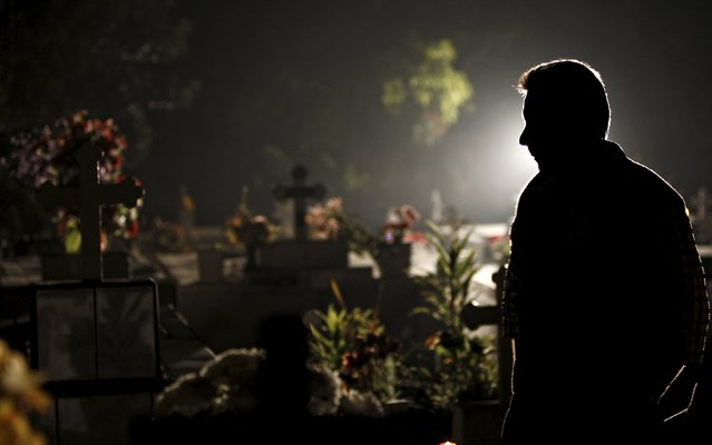 A man stands near graves as he takes part in a vigil at a cemetery in Barva de Heredia, Costa Rica October 31, 2015. (Photo by Juan Carlos Ulate/Reuters)