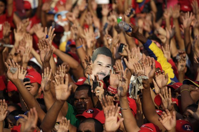 Supporters wave their hands as one of them holds a mask of Venezuela's acting President Nicolas Maduro during a campaign rally in Catia La Mar, Venezuela, Tuesday, April 9, 2013.  Maduro, the hand-picked successor of late President Hugo Chavez, is running for president against opposition candidate Henrique Capriles in the presidential election set for Sunday, April 14. (Photo by Ariana Cubillos/AP Photo)
