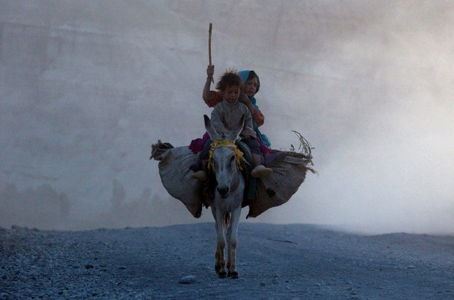Ethnic Afghan Hazara children return home on a donkey to their village on the outskirts of Bamiyan, located in central Afghanistan August 15, 2009. (Photo by Adrees Latif/Reuters)