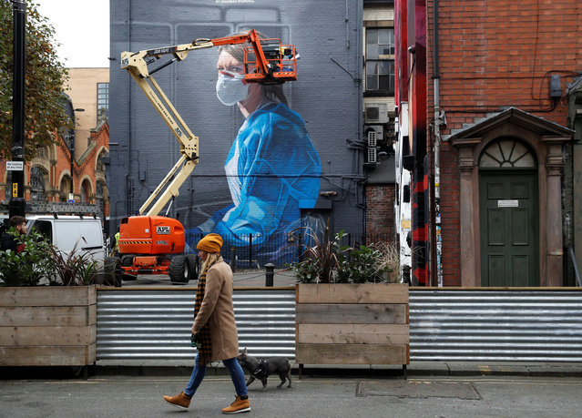 A woman walks past as an artist works on a mural during the outbreak of the coronavirus disease (COVID-19), in Manchester, Britain October 18, 2020. (Photo by Phil Noble/Reuters)