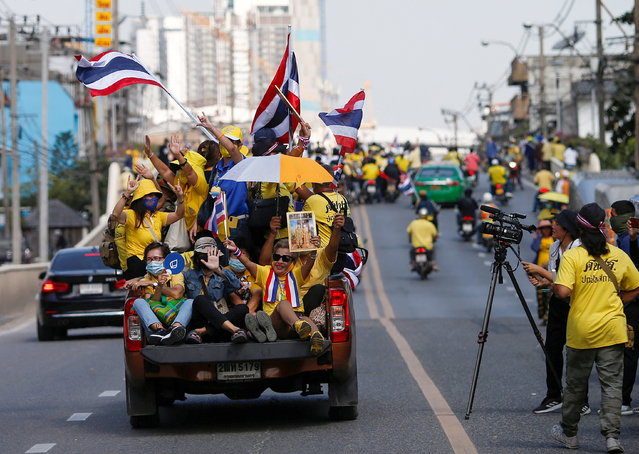 Royalists hold national flags while riding towards a rally in front of the parliament, to show their opposition towards the proposed motion to amend the Constitution on articles related to the monarchy, in Bangkok, Thailand on November 17, 2020. (Photo by Soe Zeya Tun/Reuters)