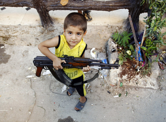 A boy plays with an AK-47 rifle owned by his father in Azaz, some 47 km (29 miles) north of Aleppo August 3, 2012. (Photo by Goran Tomasevic/Reuters)