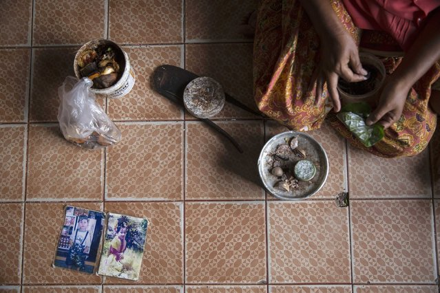 Manee, the 45-year-old wife of an unemployed fisherman from Myanmar, prepares betel nuts after showing pictures of her children killed in the 2004 tsunami at her home in Ban Nam Khem, December 13, 2014. Manee lost all her three children aged three, four and nine when tsunami hit a small fishing village on Thailand's Andaman Sea coast on December 26, 2004. (Photo by Damir Sagolj/Reuters)