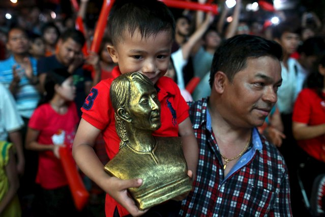 A boy carries a bust depecting Myanmar's pro-democracy leader Aung San Suu Kyi while gathering to see partial results shown on a TV outside NLD party headquarters in Yangon, November 8, 2015. (Photo by Soe Zeya Tun/Reuters)