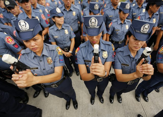 Lady officers of the Philippine National Police force show the taped muzzle of their guns at a police camp in Taguig City, south of Manila, Philippines, 22 December 2014. (Photo by Francis R. Malasig/EPA)